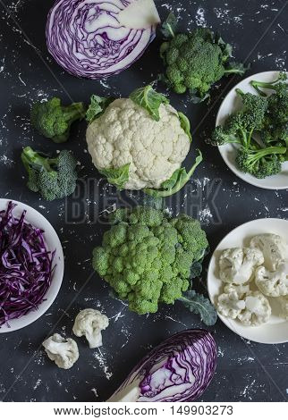 Variation of fresh cabbage - broccoli cauliflower red cabbage. On a dark background top view