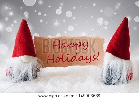 Christmas Greeting Card With Two Red Gnomes. Sparkling Bokeh And Noble Silver Background With Snow. English Text Happy Holidays