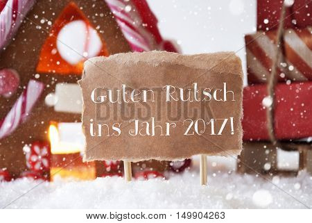 Gingerbread House In Snowy Scenery As Christmas Decoration. Sleigh With Christmas Gifts Or Presents And Snowflakes. Label With German Text Guten Rutsch Ins Jahr 2017 Means Happy New Year
