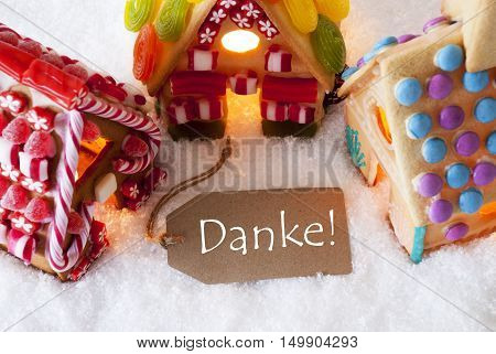 Label With German Text Danke Means Thank You. Colorful Gingerbread House On Snow. Christmas Card For Seasons Greetings