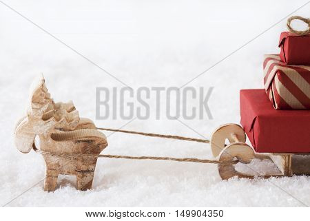 Moose Is Drawing A Sled With Red Gifts Or Presents In Snow. Christmas Card For Seasons Greetings. White Background. Copy Space For Advertisement