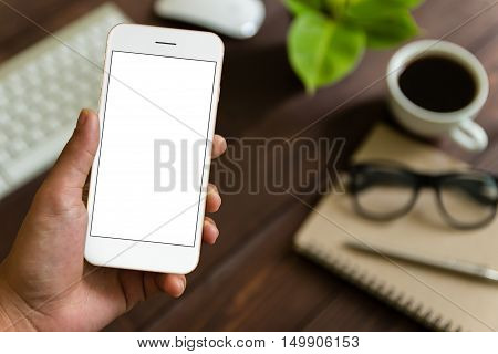close up hand holding phone over work table mockup phone blank screen for app screen adjustment