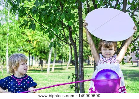 Two little sisters. Playing with butterfly net. with a sign. Park on a sunny summer day. Family time. cute kids