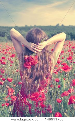 Back view of a young woman with long blonde hair in a red dress holding a bouquet of flowers in a poppy field and enjoying the beauty of nature in a warm summer day. Rear view. Pastel toned image.
