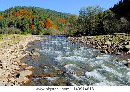 Landscape with autumn mountains trees and river