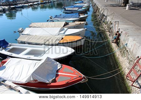 Covered small sea boats docked in a row at sea canal