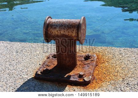 Rusted old iron mooring bollards on local pier with sea in background