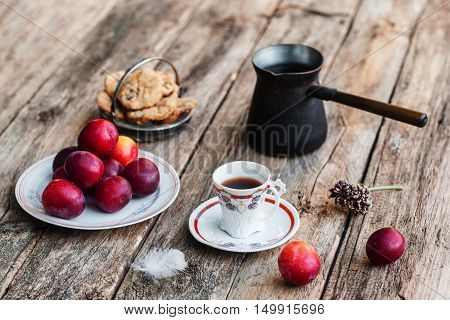 Fresh tasty autumn breakfast. Cup of coffee with cookies, fresh plums and coffee pot on old rustic wooden table