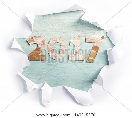 Photo of numbers forming '2017', cut out of paper with golden and white paint strokes, shot from above on light teal background, with torn paper on it. New Year greeting card or annual report design