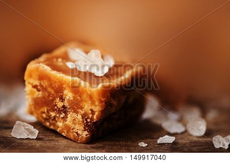 Caramel candy on brown background macro. Salted caramel piece and sea salt. Golden Butterscotch toffee caramels. Toffees.