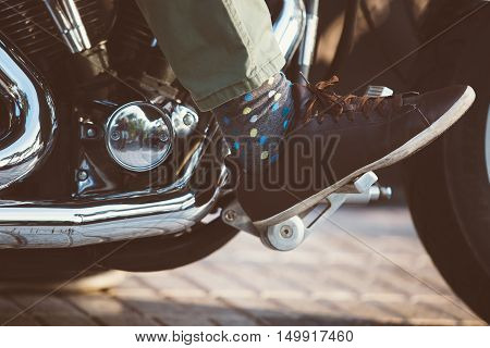 Close-up of foot in polka dot sock and leather shoe on throttle pedal of bike