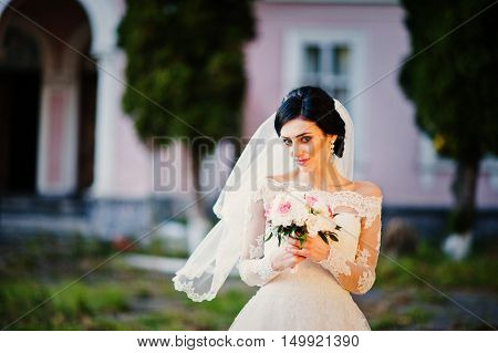 Stylish Brunette Bride Near Old Vintage Pink House With Columns