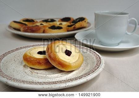 Homemade cakes with cottage cheese with raisin on the plate in the background a plate with different cakes with jam and poppy seeds cup of black coffee on the table