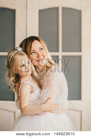 Mother and daughter like brides in white dress hugging.