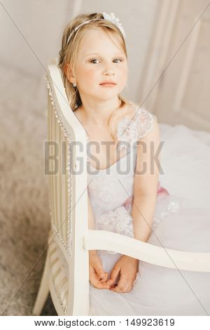 Little princess like a bride sitting on the chair.