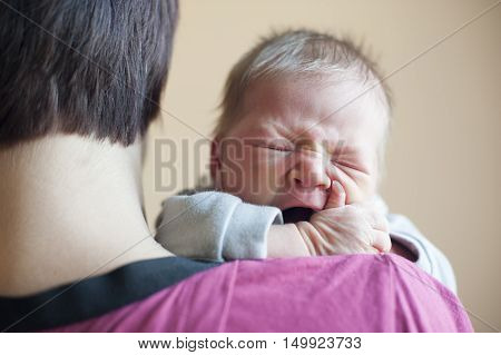 The newborn girl on hands at mum