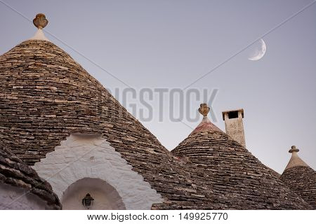 Trulli with moon at sunset in Alberobello (Italy)