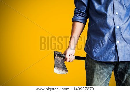 A guy holding old rusty axe, close up front view, on yellow background with copy space