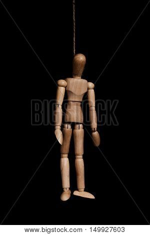 Low key, wooden puppet marionette hangman by rope, on black background