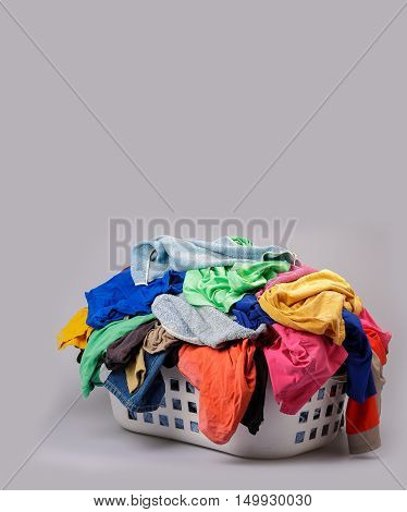 Pile of bright multicolored laundry in a plastic wash basket in the colors of the rainbow in a concept or domestic hygiene and household chores on grey with copy space