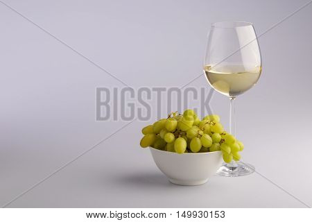 Elegant glass of white wine with a bunch of fresh green grapes in a bowl in a concept of wine making and viticulture on a grey background with copy space