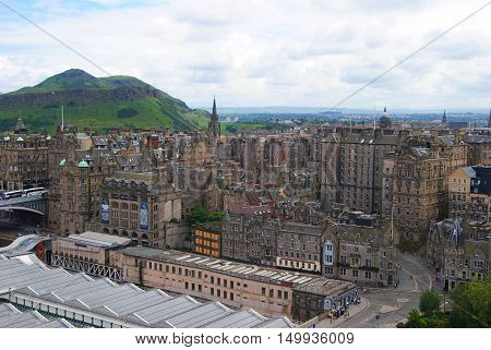 Edinburg, United Kingdom - June 14, 2014. View over Edinburgh towards Salisbury Crags, with historic buildings, Arthurs Seat and people.