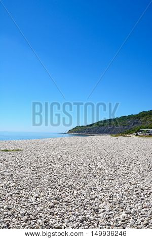 View along the pebbly beach with the mountainous cliffs of the Jurassic coast to the rear Lyme Regis Dorset England UK Western Europe.