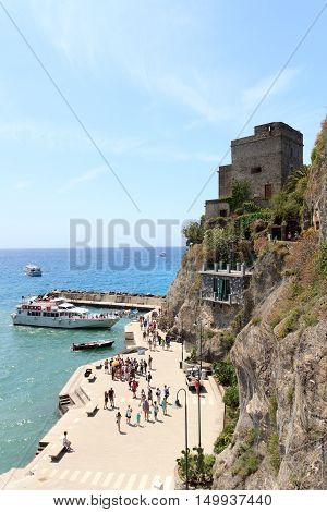 Monterosso, Italy - June 26, 2016: Port in Cinque Terre village Monterosso al Mare, Torre aurora and Mediterranean Sea. Monterosso is one of the five villages in Cinque Terre. The Torre Aurora is a famous watchtower.