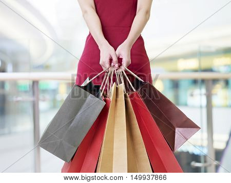 young woman female shopper standing with colorful paper bags in hands in shopping mall or department store focus on hands