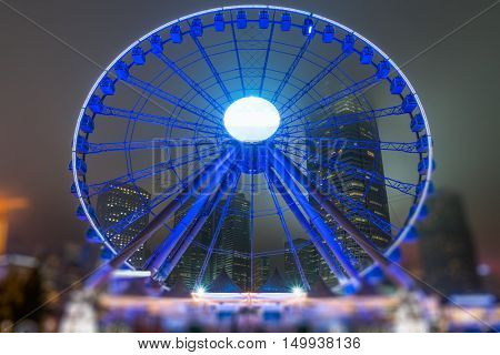 illuminated observation wheel front of skyscrapers at victoria harbor,Hong Kong,china,east asia.