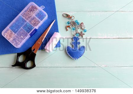 Blue felt anchor keychain with beads. Handmade charm keychain for beach bags, scissors, box of beads, white thread, needle on wooden background. Summer sewing DIY idea
