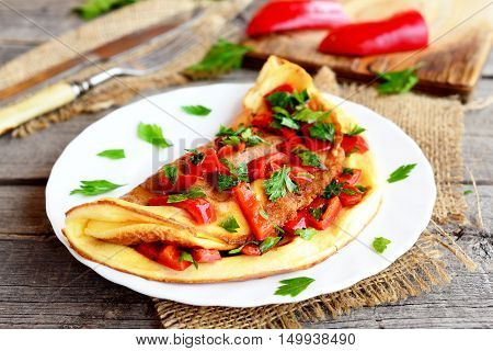 Omelette with vegetables on a plate, fork and knife on old wooden background. Colorful omelette stuffed with roasted red pepper and chopped fresh parsley. Breakfast egg recipe. Closeup