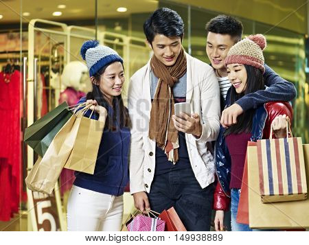 two asian couples using cellphone and sharing information while shopping for christmas in mall or department store