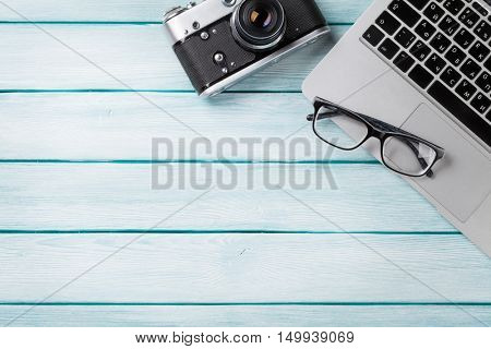 Desk table with laptop and camera on wooden table. Workplace. Top view with copy space.