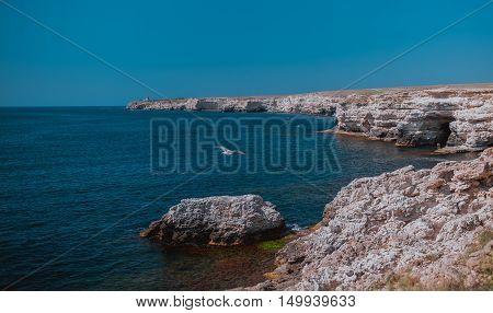 Summer view cliffed seacoast. The marine rocks landscape.. Blue sea and sky, seagal flies, beautiful nature. Black Sea bay, Crimea.