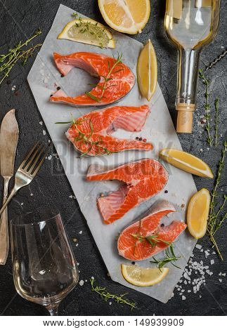 Steak of fresh salmon with lemon, aromatic herbs and white wine . Top view.