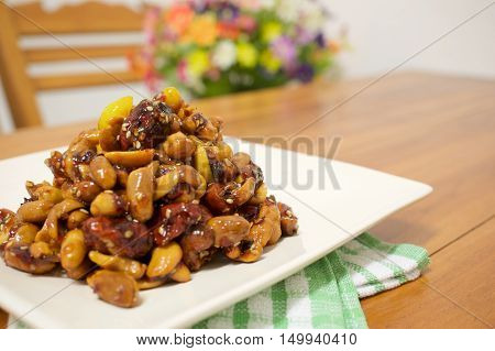 Fried chinese jujube and cashew nut vegetarian include gingko and nut with sesame on white plate with green fabric on wood table and blur flower as background.