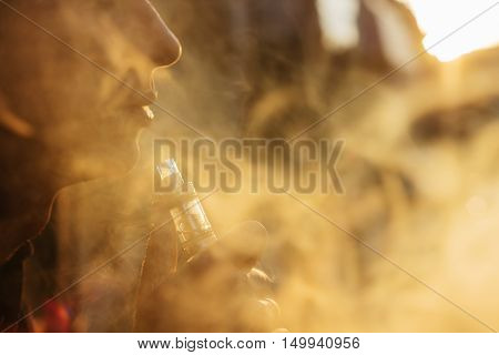 Man Using Vape Or Electronic Cigarette Against The Background Of