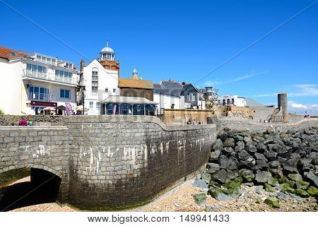 LYME REGIS, UNITED KINGDOM - JULY 18, 2016 - Seafront wall and bridge along Gun Cliff Walk with the Lyme Regis Museum and town buildings to the rear Lyme Regis Dorset England UK Western Europe, July 18, 2016.