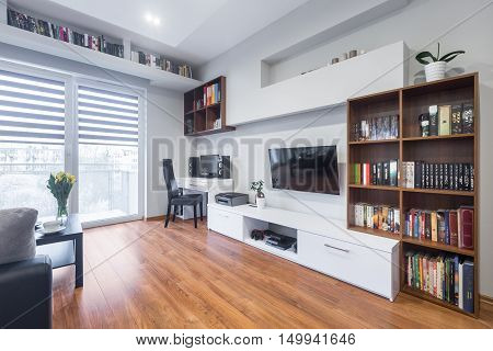 Light and spacious living room with window TV bookshelves floor panels and modern furniture