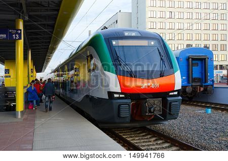 MINSK BELARUS - OCTOBER 1 2016: Unidentified people are waiting to board in electric train of business class EPM-001 of company Stadler (line Minsk-Gomel) on platform of railway station Minsk Belarus