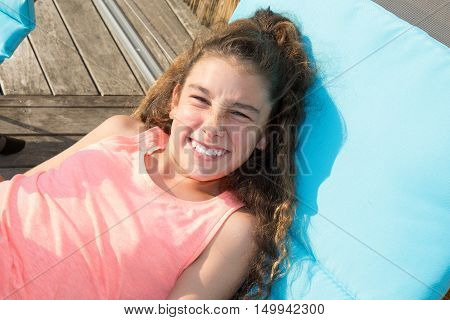 Close Up Portrait Of Young Girl Lying Down On Deck Chair