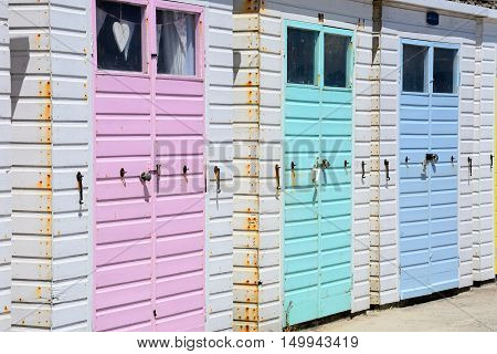 Row of colourful beach huts along the edge of the beach and promenade Lyme Regis Dorset England UK Western Europe.