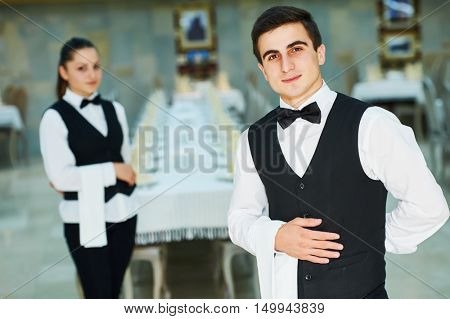 young waiter and waitress at service in restaurant