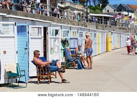 LYME REGIS, UNITED KINGDOM - JULY 18, 2016 - Row of colourful beach huts along the edge of the beach and promenade with tourists enjoying the setting Lyme Regis Dorset England UK Western Europe, July 18, 2016.