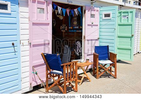 LYME REGIS, UNITED KINGDOM - JULY 18, 2016 - Wooden table and chairs outside a beach hut along the edge of the beach and promenade Lyme Regis Dorset England UK Western Europe, July 18, 2016.