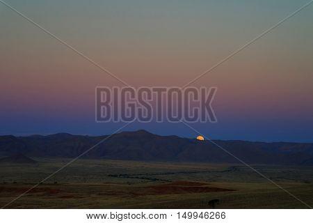 Full moon ascends over the dune in Namib desert