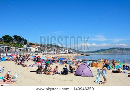 LYME REGIS, UNITED KINGDOM - JULY 18, 2016 - Holidaymakers relaxing on the sandy beach with the promenade and beach huts to the rear Lyme Regis Dorset England UK Western Europe, July 18, 2016.