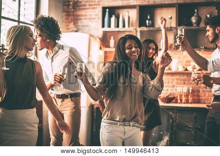 Just keep moving! Cheerful young people dancing and drinking while enjoying home party on the kitchen