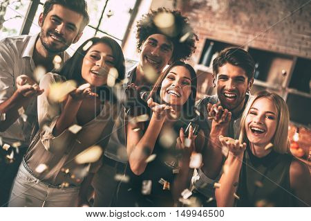 Confetti fun. Cheerful young people blowing confetti and smiling while enjoying party together